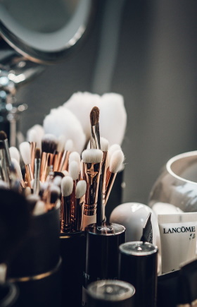 Photo of a collection of high end makeup brushes on a vanity depicting luxury skincare and makeup