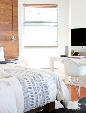 Photo of the inside of a city apartment with a bed and Mac computer in frame depicting luxurious home decor and furniture