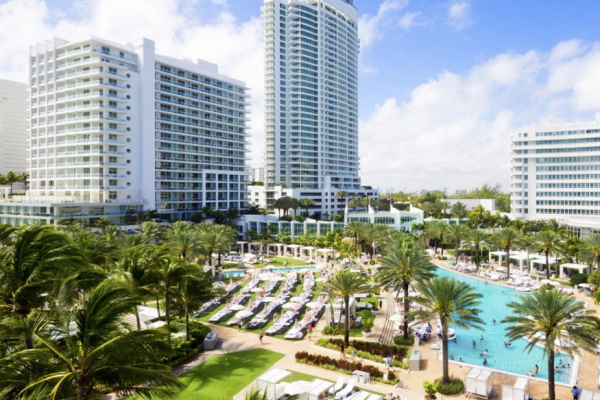 Image of Fontainebleau girlfriend getaway destination in Miami Beach taken from a distance showing building and pool surrounded by palm trees