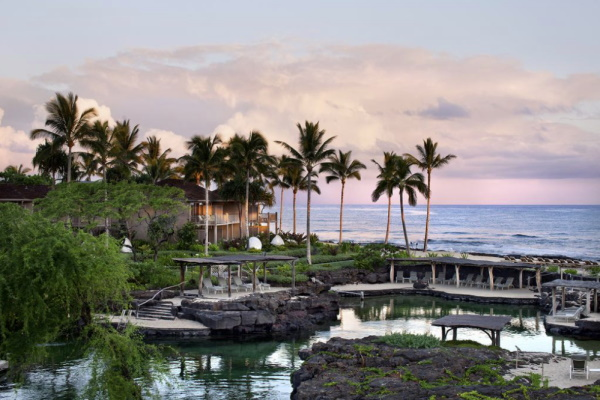 Photo of the ocean and a pond surrounded by palm trees as the sun sets at Four Seasons Resort Hualalai in Hawaii