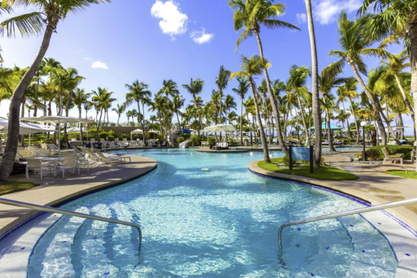 Image of a gorgeous pool surrounded by palm trees at the girlfriend getaway resort Hilton Ponce Golf & Casino Resort in Puerto Rico