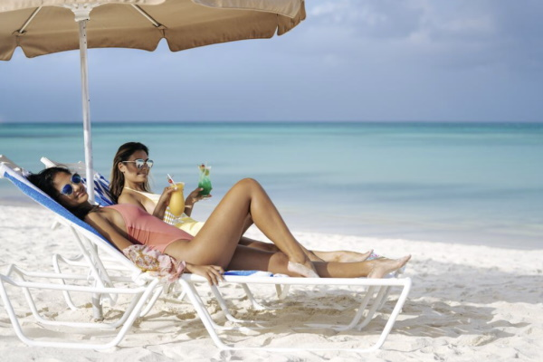 Image of two girls sitting on lounge chairs by the ocean on a girlfriend getaway at all inclusive Holiday Inn Resort Aruba