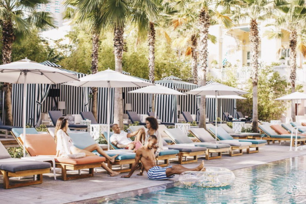 Image of people sitting by the pool at SLS Baha Mar in Nassau, Bahamas