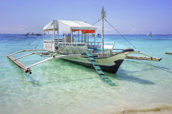 Image of a boat floating on crystal clear blue waters in vacay destination Boracay Philippines