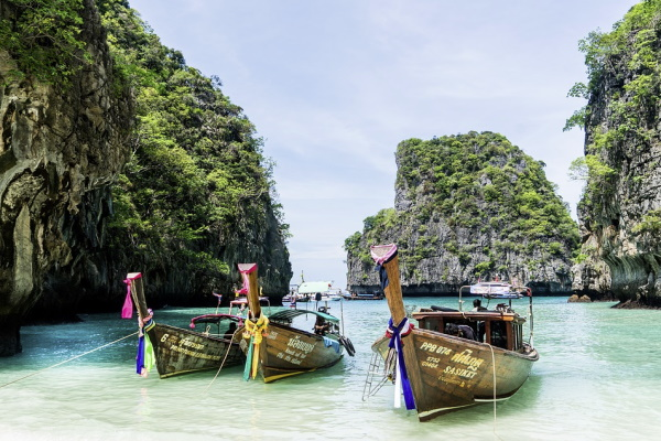 Image of the iconic boats docked in Phuket Thailand as an exotic vacation idea