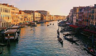Image of an alleyway in Italy, showing boats and buildings as the sun sets and displaying luxury travel destinations across the world