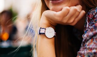 Image of a woman smiling and wearing a watch to illustrate luxury gift ideas for her